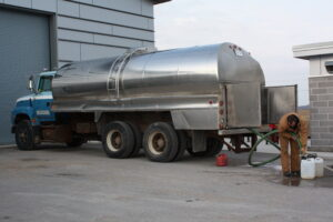 A water hauler is delivering a load of drinking water into a storage tank.